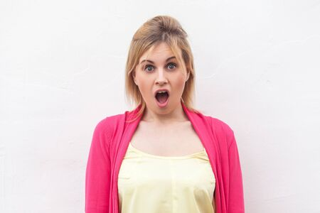 Portrait of shocked beautiful blond young woman in yellow shirt and red blouse standing and looking at camera with surprised face. indoor studio shot, isolated on white wall background. Stock Photo