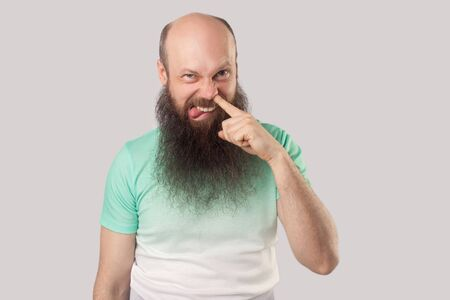 Portrait of funny dirty middle aged bald man with long beard in light green t-shirt standing drilling with finger on his nose, tongue out and looking. indoor studio shot, isolated on grey background. Stock Photo