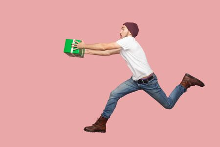 Side view of portrait of crazy bearded young hipster man in white shirt and casual hat jumping, running and hurry up with delivery green present. Indoor, isolated, studio shot, pink background