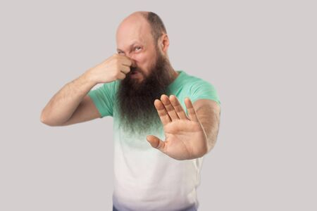 Bad smell, stop. Portrait of confused middle aged bald man with long beard in light green t-shirt standing, blocking his nose and showing stop gesture. indoor studio shot, isolated on grey background Stock Photo