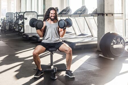 Portrait of grimace young adult muscular built athlete with long curly hair working out in gym, sitting on weightlifting machine, holding two dumbbell with raised arms, swing shoulders. indoor, roar