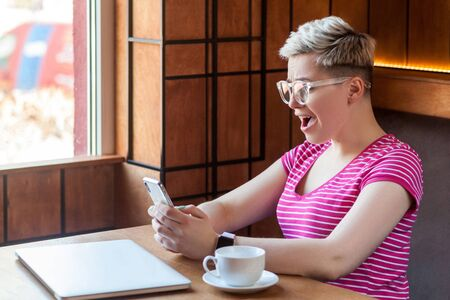 Side view portrait of shocked screaming young blogger with blonde short hair in pink t-shirt is sitting in cafe, holding phone with opened mouth, reading unbelievable news. Indoor, healthy lifestyle