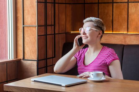 Portrait of beautiful satisfied happy young bussineswoman with blonde short hair in pink t-shirt is sitting in cafe, talking on phone with toothy smile, looking at window. Indoor, healthy lifestyle