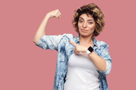 Portrait of strong proud young woman with curly hairstyle in casual blue shirt standing and pointing at her biceps to show her independent or feminism. indoor studio shot, isolated on pink background. Stock Photo