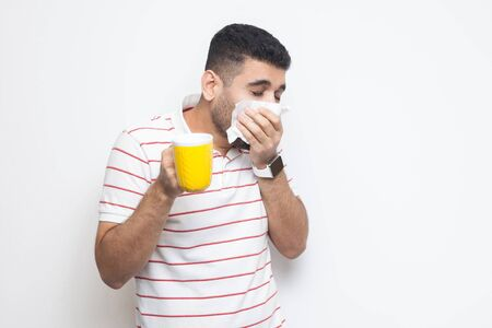 Cold and flu. Portrait of sick bearded young man in striped t-shirt standing, holding tissue, cleaning his nose, holding hot drink, try to be treated. indoor studio shot, isolated on white background.