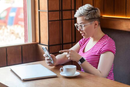 Side view portrait of excited young blogger with short hair in pink t-shirt is sitting in cafe, holding phone and making video call with shocked face, pointing finger at screen. Indoor, lifestyle