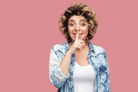Portrait of worry young woman with curly hairstyle in casual blue shirt standing, telling secret and looking at camera with finger on lips secret sign. indoor studio shot, isolated on pink background. Stock Photo
