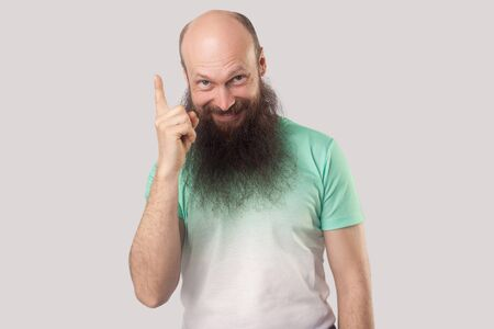 Idea. Portrait of excited middle aged bald man with long beard in t-shirt standing, holding his finger up in idea gesture and looking at camera smiling. indoor studio shot isolated on grey background