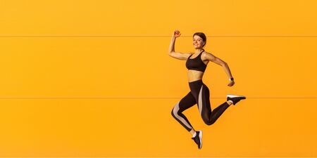 Side view of young satisfied attractive sporty woman in fashionable black sportswear runner in on orange wall background. Dynamic jumping movement. Sport, healthy lifestyle and happiness concept. Stock Photo