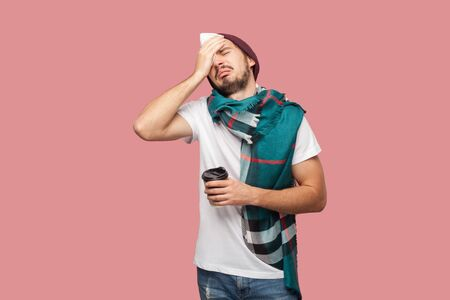Sickness modern bearded young hipster man in white shirt, hat and scarf standing, touching with hand his head, have strong headache, holding hot tea in cup. Indoor,isolated,studio shot,pink background