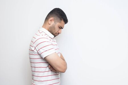 Profile side view portrait of sad alone o depressed bearded young man in striped t-shirt standing, holding his head down and feeling bad or thinking. indoor studio shot, isolated on white background.