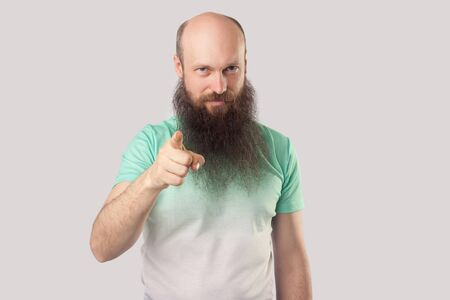 Hey you! Portrait of serious middle aged bald man with long beard in light green t-shirt standing, pointing and looking at camera. indoor studio shot, isolated on grey background. Stock Photo