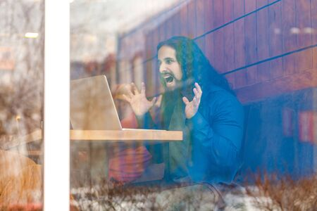 Portrait through the window of angry aggressive young adult man freelancer in casual style sitting in cafe, trying to crash laptop screen, raised arms with clenching teeth. Outdoor, lifestyle concept Stock Photo
