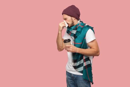 Portrait of sickness modern bearded young hipster man in white shirt and casual hat standing,sneezes of napkin, holding hot drink in paper cup. Indoor, isolated, studio shot, pink background