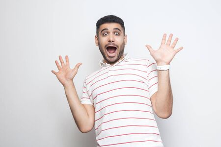 Portrait of surprised handsome bearded young man in striped t-shirt standing with raised arms and looking at camera with amazed shocked face. indoor studio shot, isolated on white background.