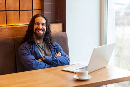 Satisfied handsome bearded young man freelancer in casual style sitting in cafe with laptop, crossing arms and looking at camera with toothy smile, bussinessman in office. Indoor, lifestyle concept