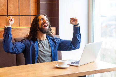 Portrait of happy screaming handsome young adult man freelancer in casual style sitting in cafe and with laptop, celebrate the goal of fooftball match, bussinessman in office. Indoor,lifestyle concept
