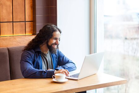 Portrait of handsome happy bearded young adult man freelancer in casual style sitting in cafe and chating with his friend in laptop, bussinessman in office, toothy smile. Indoor, lifestyle concept