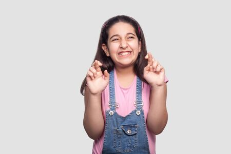 Portrait of hopeful beautiful brunette young girl in casual style, pink t-shirt and blue denim overalls standing with crossed fingers and clenching teeth. studio shot isolated on light gray background Stock Photo