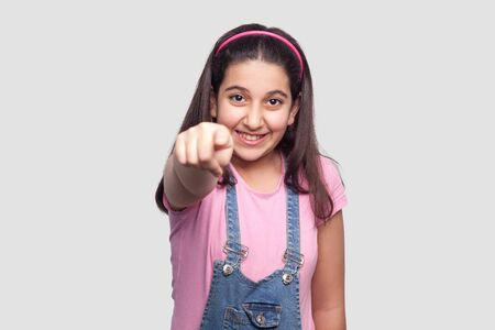 Portrait of happy beautiful brunette young girl in casual pink t-shirt, blue denim overalls standing, looking and pointing at camera with toothy smile. studio shot, isolated on light gray background.