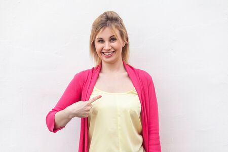 Portrait of happy satisfied beautiful blond young woman in yellow shirt and red blouse standing pointing herself and looking at camera with toothy smile. studio shot, isolated on white wall background Stock Photo