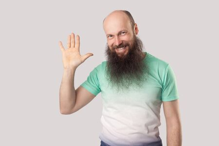 Portrait of happy middle aged bald man with long beard in light green t-shirt standing looking with toothy smile and waving his hand and greeting. indoor studio shot, isolated on grey background. Stock Photo