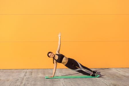 Young sporty attractive woman practicing yoga, doing vasisthasana exercise, side plank pose, working out on green mat, wearing black sportswear, Outdoor, orange background, sport and healthy concept