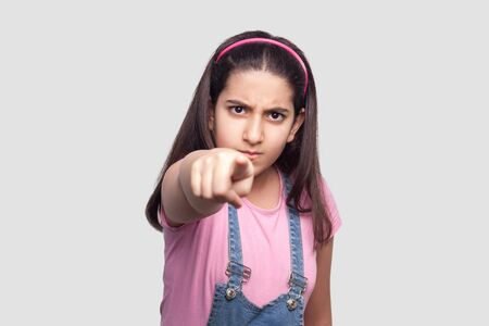 Hey you! Portrait of serious brunette young girl in casual style, pink t-shirt and blue denim overalls standing, blame, looking and accusing at camera. studio shot, isolated on light gray background. Stock Photo