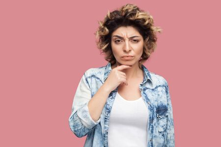 Portrait of thoughtful young woman with curly hairstyle in casual style standing, touching her chin and looking at camera with confused thinking face. indoor studio shot, isolated on pink background. Stock Photo