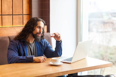 I need more. Portrait of handsome intelligence young adult man freelancer in casual style sitting in cafe and looking at laptop display and asking, bussinessman in office. Indoor, lifestyle concept