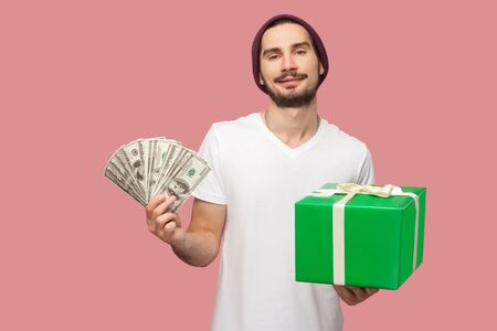 Portrait of happy handsome bearded young hipster man in white shirt and casual hat standing, holding fan of cash dollars and green present box. Indoor, isolated, studio shot, pink background