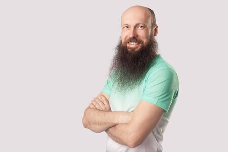 Portrait of happy satisfied middle aged bald man with long beard in green t-shirt standing with crossed arms and looking at camera with toothy smile. indoor studio shot, isolated on grey background. Stock Photo