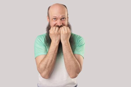 Portrait of nervous middle aged bald man with long beard in light green t-shirt standing, bitting his nails and looking at camera with worry panic face. indoor studio shot isolated on grey background Stock Photo