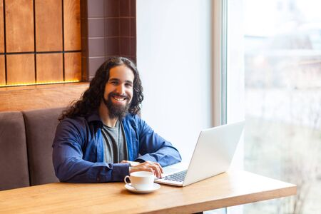 Portrait of satisfied handsome intelligence bearded young adult man freelancer in casual style sitting in cafe and working in laptop,looking at camera, bussinessman in office. Indoor,lifestyle concept Stock Photo