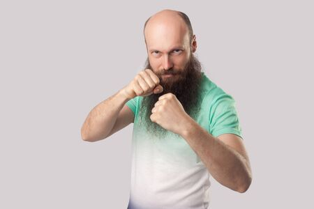 Portrait of serious middle aged bald man with long beard in light green t-shirt standing in boxing fists and looking at camera and ready to punching. indoor studio shot, isolated on grey background. Stock Photo