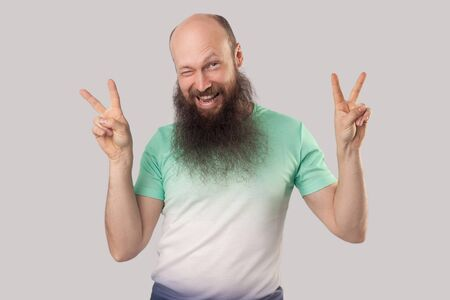 Portrait of funny middle aged bald man with long beard in light green t-shirt standing with victory or peace gesture and looking and winking. indoor studio shot, isolated on grey background.