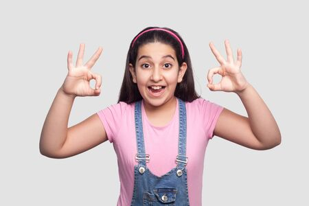 Portrait of amazed beautiful brunette young girl in casual style, pink t-shirt and blue denim overalls standing with Ok sign and looking at camera. indoor studio shot isolated on light gray background