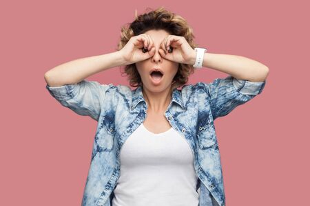 Portrait of shocked funny young woman with curly hair in blue shirt standing with binoculars gesture hands on eye and looking at camera with amazed face. indoor studio shot isolated on pink background