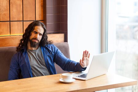 Stop talking! Serious handsome young adult man freelancer in casual style sitting in cafe and talking with his opponent in laptop, showing hand to notebook like to stop. Indoor, lifestyle concept