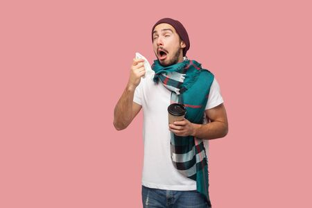 Sickness modern bearded young hipster man in white shirt, hat and scarf standing, sneezes on napkin with opened mouth, holding hot tea in paper cup. Indoor, isolated,studio shot, pink background