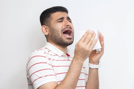Cold and flu. Portrait of sick bearded young man in striped t-shirt standing, holding tissue and sneezing. indoor studio shot, isolated on white background.