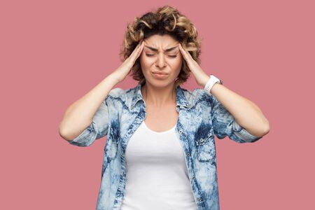 Headache, thinking or confusion. Portrait of sad young woman with curly hair in casual blue shirt standing and holding her painful head with closed eyes. indoor studio shot isolated on pink background