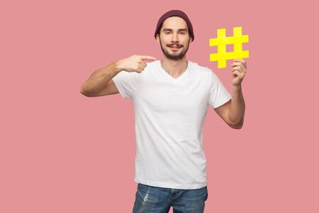 Portrait of happy handsome bearded young hipster man in white shirt and casual hat standing, holding yellow hashtag and pointing finger to it. Indoor, isolated, studio shot, pink background