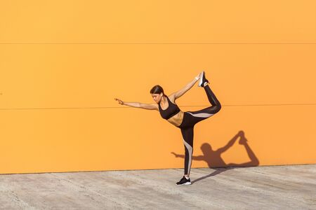 Young attractive girl practicing yoga, standing in natarajasana exercise, holding balance, working out, wearing black sportswear, urban style, full length, orange background, outdoor sport concept