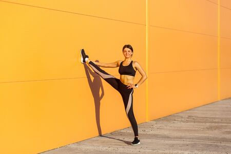 Young attractive sporty woman wearing black sporwear practicing sport exercises in morning on street, showing perfect twine on orange wall background, looking at camera with toothy smile, outdoor Stock Photo