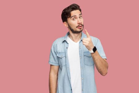 Portrait of serious handsome bearded young man in blue casual style shirt standing with warming sign and looking at camera to give attention. indoor studio shot, isolated on pink background.
