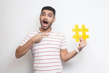 New social media concept. Positive young adult man in t-shirt holding large big yellow hashtag sign and pointing with finger to it with amazing face. Indoor, isolated, studio shot, white background 写真素材