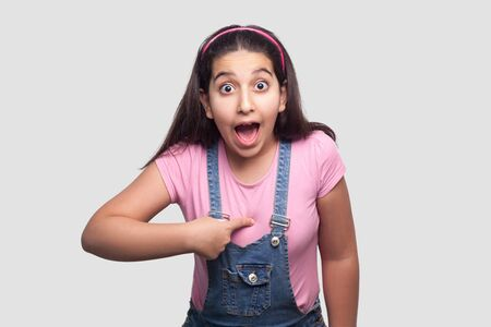 who? me? Portrait of shocked brunette girl in casual pink t-shirt and blue overalls standing, pointing herself, looking at camera with surprised face. studio shot, isolated on light gray background. Stock fotó