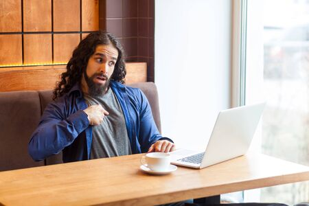 Portrait of excited handsome young adult man freelancer in casual style sitting in cafe and talking with his friend in laptop, pointing finger to himself with suprised face. Indoor, lifestyle concept