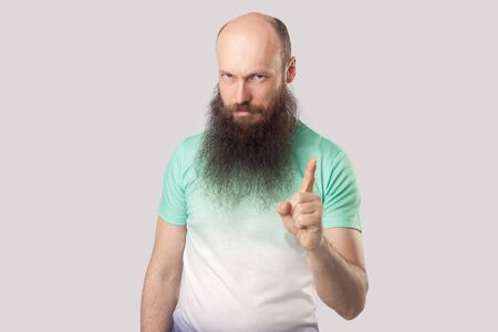 Portrait of serious bossy middle aged bald man with long beard in light green t-shirt standing with warning gesture and looking at camera and alarming. indoor studio shot, isolated on grey background